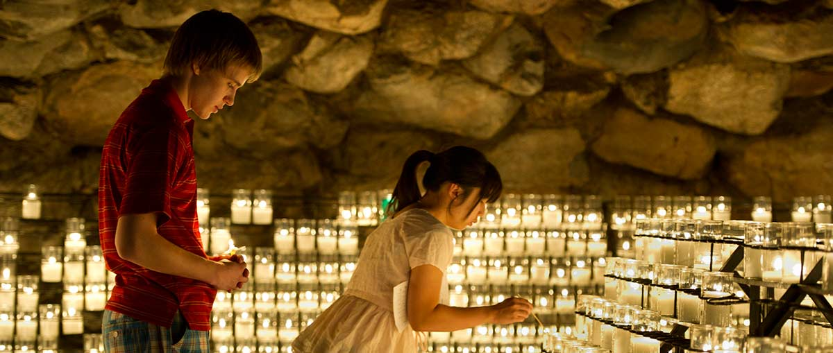 Students lighting candles at the Grotto